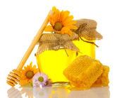 Sweet honey in jars with honeycomb, wooden drizzler and flowers isolated on white — Stock Photo