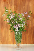 Bouquet of vicia in a transparent vase on wooden background — Stock Photo