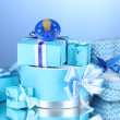 Beautiful gifts, baby's bootees and dummy on blue background - Stok fotoğraf