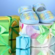 Beautiful gifts and baby's bootees on blue background - Stok fotoğraf