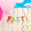 Party. Balloons against a wooden fence on sky background - Stock Photo