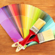 Paint brushes and bright palette of colors on wooden background — 图库照片