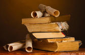 Pile of old books and scroll on brown — Stock Photo
