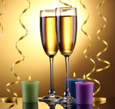 Glasses of champagne, candles and streamer on yellow background — Stock Photo