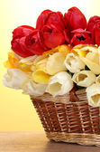 Beautiful tulips in basket on wooden table on yellow background — Stock Photo
