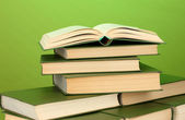 Pile of books on green background close-up — Stockfoto