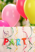 Party. Balloons against a wooden fence on green background — Stock Photo