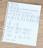 Math on copybook page on a wooden table — 图库照片