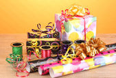 Gigts, paper, ribbon and bows on wooden table on yellow background — Stock Photo