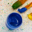 Jar with a blue gouache with brushes on colorful splashes background close-up — Foto de Stock