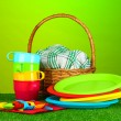Bright plastic disposable tableware and picnic basket on the lawn on colorful background — Stock Photo #11104814