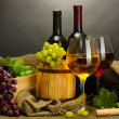 Barrel, bottles and glasses of wine and ripe grapes on wooden table on grey background — Stockfoto #11104883