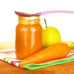 tarro con zanahoria y manzana bebé comida, cuchara y zanahorias y manzanas en servilleta colorida en primer plano de fondo blanco — Foto de Stock