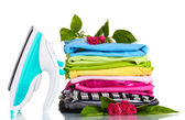 Pile of colorful clothes and electric iron with roses isolated on white — Stock Photo
