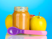 Jar with fruit baby food and spoon on colorful background — Stock Photo