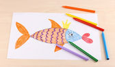 Children's drawing of golden fish and pencils on wooden background — Stock Photo