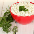 Cottage cheese with parsley and dill in red bowl on white wooden table close-up — Stock Photo