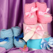 Pink and blue baby boots, pacifier and gifts on silk background — Stock Photo