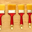 Paint brushes on wooden background — Stock Photo #11139371