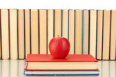 Pile of books with an apple on white background close-up — Zdjęcie stockowe