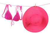 Women's bra swimsuit and hat hanging on a rope on white background — Stock Photo