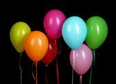 красочные воздушные шары, изолированные на черном фоне — Стоковое фото