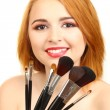 Portrait of beautiful woman with make-up brushes — Stock Photo