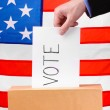 Hand with voting ballot and box on Flag of USA — Stock Photo #11159800