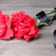 Carnations and black ribbon on grey wooden background - Stock Photo