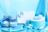 Beautiful gifts, baby's bootees, blank postcard and dummy on blue silk — Stock Photo