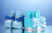 Beautiful gifts and baby's bootees on blue background — Stock Photo
