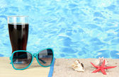 Beach composition of fashionable women's sunglasses and a refreshing drink — Stock Photo