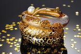 Mooie gouden armbanden op grijze achtergrond — Stockfoto