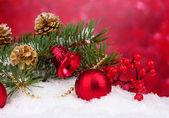 árbol de navidad bolas y verde en la nieve en rojo — Foto de Stock