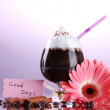 Glass of coffee cocktail and gerbera flower on purple background — Stock Photo