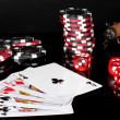 Four of a kind with poker chips and dice on black background — Stock Photo #11160115
