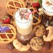 Glasses of coffee cocktail on wooden table with sweet and flowers - Stock Photo