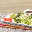 Tasty rolls served on white plate with chopsticks on grey mat on light background — Foto de Stock