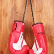 Red boxing gloves hanging on wooden background — Stock Photo #11160715