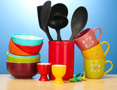 Bright empty bowls, cups and kitchen utensils on wooden table on blue background — Stock Photo