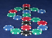 Poker chips in the form of dollars on a blue table — Stock Photo