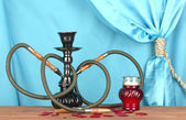 Hookah on a wooden table on a background of blue curtain close-up — Foto Stock