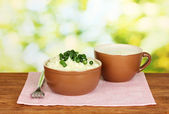 Mashed potato in the bowl and cup with milk on colorful napkin on wooden background — Stock Photo