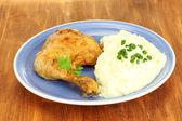Pečené kuřecí stehno s bramborovou kaší v talíř na dřevěný stůl detail — Stock fotografie
