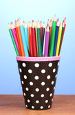 Color pencils in glass on wooden table on blue background — Stock Photo