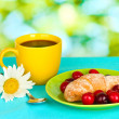 Croissant with cherries and coffee on wooden table on green background — Stock Photo #11176020
