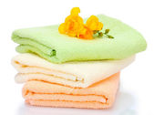Colorful towels and flowers isolated on white — Stock Photo