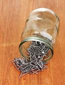 金属铁钉和玻璃罐木制背景上 — 图库照片