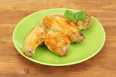 Roasted chicken wings with parsley in the plate on wooden background close-up — Stock Photo