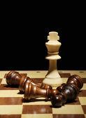 Schackbräde med schackpjäser isolerade på svart — Stockfoto